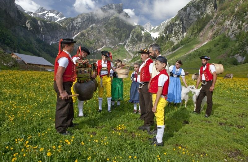 Children and Alpine herdsmen wearing traditional costume gather on an alpine pasture with Mt. Santis is the background.