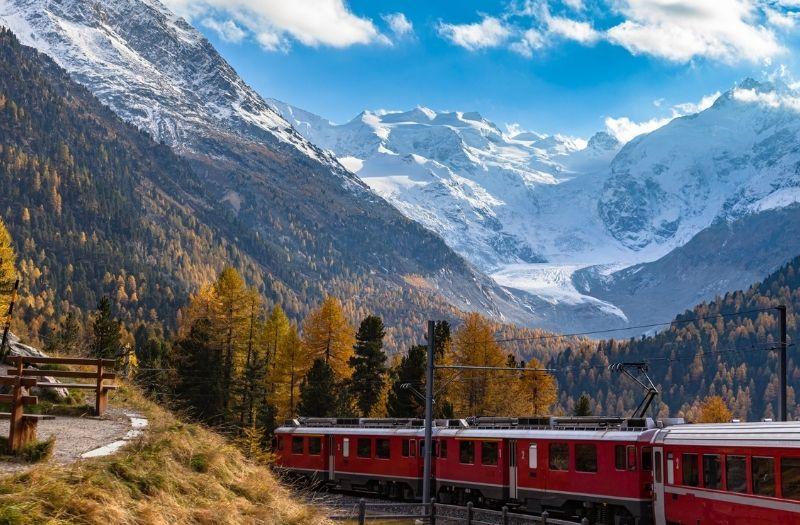 A Rhaetian Railways train passes the Morteratsch Glacier in Graubunden, Switzerland.