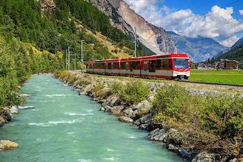 Train beside river in Switzerland
