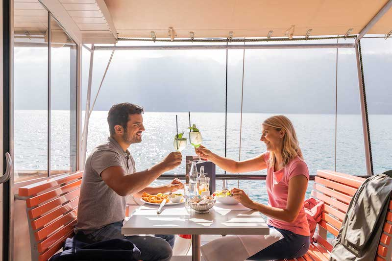 A couple eat lunch whilst cruising on Lake Lucerne.