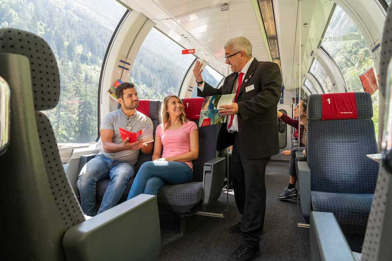A tour guide talks to passengers onboard the Gotthard Panorama Express.